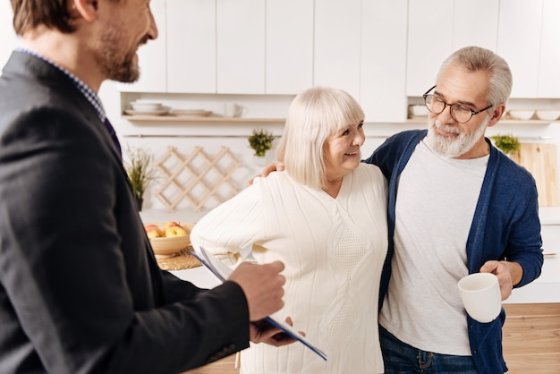 Pomagamy naszemu starszemu pokoleniu. biegle zachwycony, uśmiechnięty radca prawny spotykający się i prezentujący zgodę starszej parze klientów, wyrażający jednocześnie pozytywne nastawienie