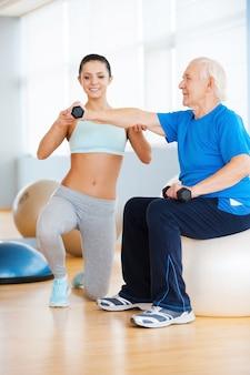 Pomagamy zachować zdrowie. pewna siebie trenerka osobista pomagająca starszemu mężczyźnie z ćwiczeniami siłowymi