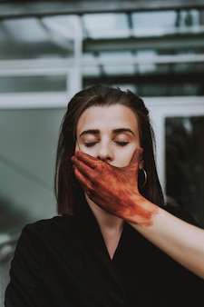 Pomalowana na czerwono ręka zakrywająca usta kobiety z zamkniętymi oczami. pojęcie ciszy