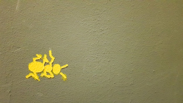 Pomalowana na żółto mrówka na szarej ścianie. mrówka wspina się po ścianie. kolorowe mrówki tła. miejscowi artyści ozdabiają ściany ulic.