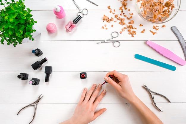 Pomaluj własne paznokcie. zestaw do manicure i lakier do paznokci na drewnianym tle. widok z góry. skopiuj miejsce. martwa natura. pielęgnacja paznokci.