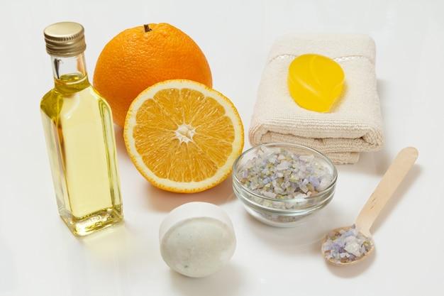 Pomarańcza cięta w całości, ręcznik frotte, butelka z olejkiem do aromaterapii, mydło, kula do kąpieli i drewniana łyżka z solą morską na białej powierzchni