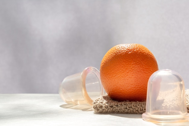 Pomarańcza leży na siatkowej myjce z naturalnych włókien, a obok niej są banki próżniowe