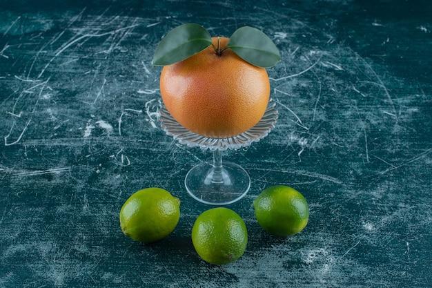 Pomarańcza na szklanym cokole obok cytryn, na marmurowym stole.
