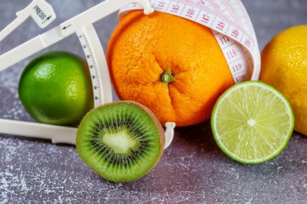 Pomarańcza owinięta miarką i suwmiarką otoczona świeżymi owocami na szarym betonowym tle. koncepcja wyszczuplenia, usunięcia cellulitu, nadania figurze kształtu.