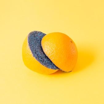 Pomarańcza przecięta na pół i obsypana pośrodku niebieskimi cekinami na żółtym tle. owocowy letni futurystyczny surrealistyczny pomysł.