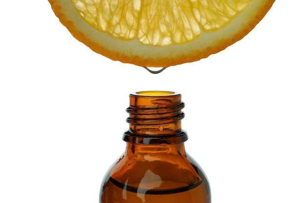 Pomarańcza z kroplą soku nad butelką na białym stole