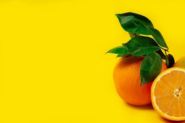 Pomarańcza z liśćmi, owocami, na pomarańczowym tle, widok z góry, bez ludzi, poziomy. wysokiej jakości zdjęcie