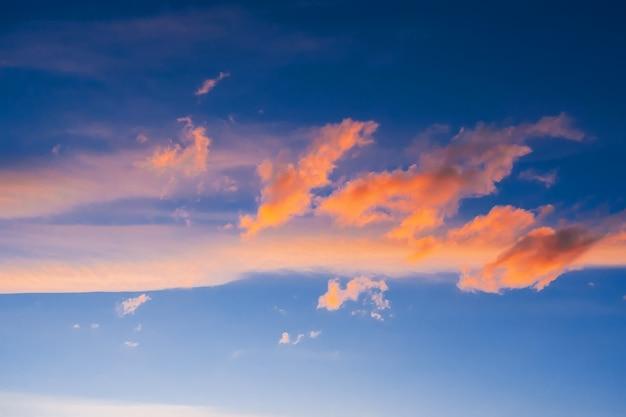 Pomarańcze chmurnieje na niebieskim niebie przy zmierzchem lub wschodem słońca