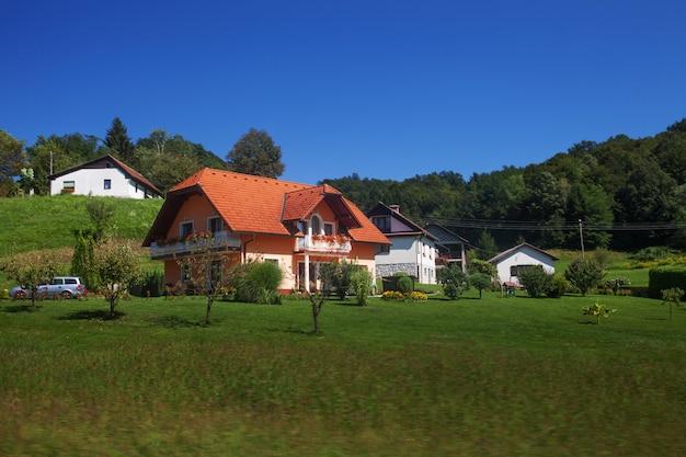 Pomarańcze domowa europa wieś wśród bujny zieleni lata krajobrazu i niebieskiego nieba