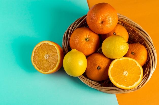 Pomarańcze i cytryna w łozinowym koszu na stole