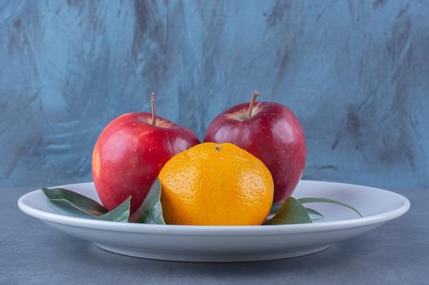 Pomarańcze i jabłka z liśćmi na talerzu na ciemnej powierzchni
