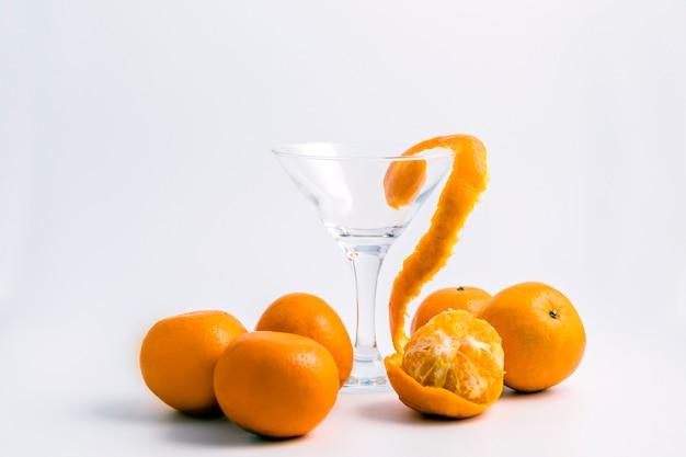 Pomarańcze i kieliszek do wina na białym stole.
