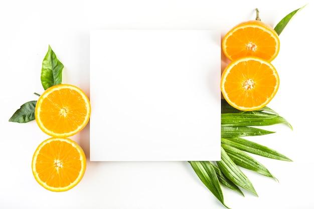 Pomarańcze i liście w pobliżu arkusza papieru