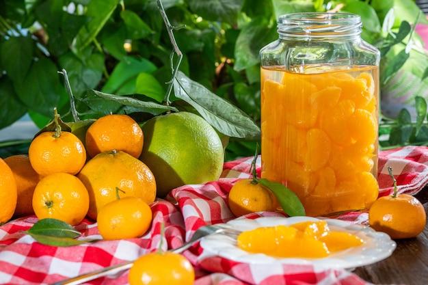 Pomarańcze i pomarańcze w puszkach na zielono-różowym talerzu w kratę
