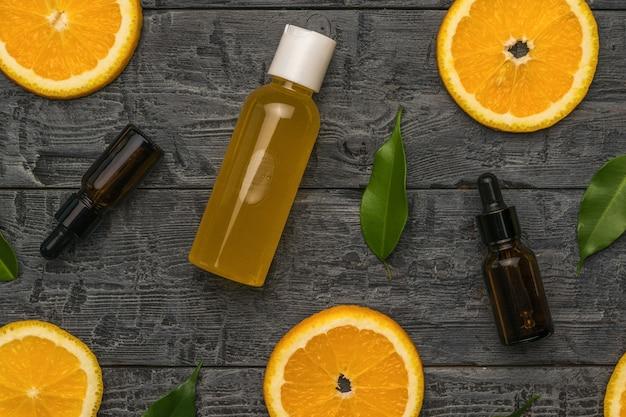 Pomarańcze, liście, butelki z zakraplaczem i butelka soku na drewnianym tle. pojęcie terapii naturalnymi środkami.