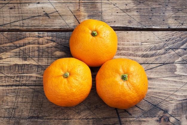 Pomarańcze mandarynki lub mandarynki klementynki, owoce cytrusowe na rustykalnym drewnianym stole