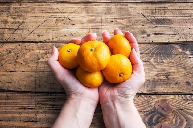 Pomarańcze mandarynki lub mandarynki klementynki, owoce cytrusowe w kobiecych rękach na drewnianym stole.
