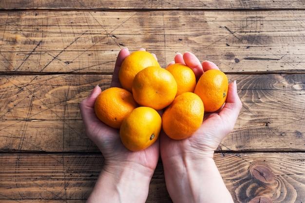 Pomarańcze mandarynki lub mandarynki klementynki, owoce cytrusowe w ręce kobiety na drewnianym stole.