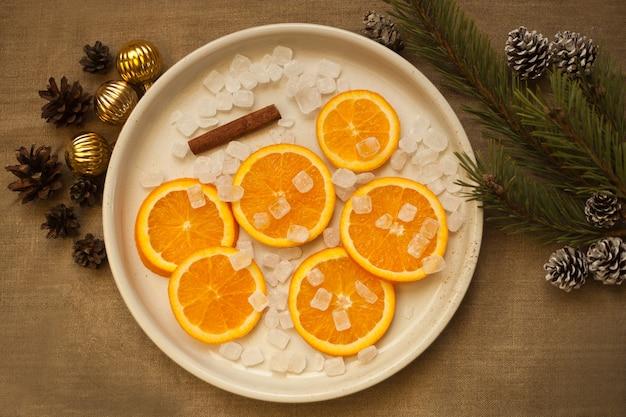 Pomarańcze na talerzu w pobliżu gałęzi choinki, złote kule i szyszki. dekoracje mandarynkowe