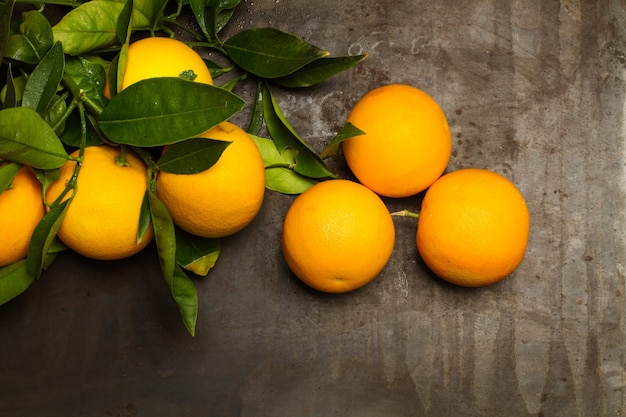Pomarańcze na zardzewiałym metalowym stole na ciemnym tle