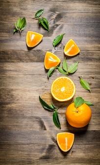 Pomarańcze świeże w całości, cięte i liście. na drewnianym stole. widok z góry