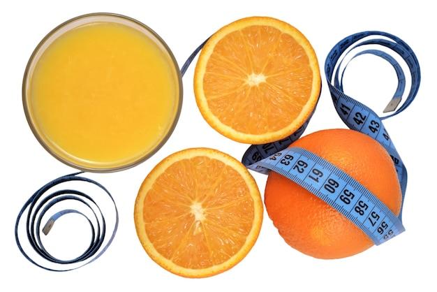 Pomarańcze, szklanka soku pomarańczowego i miarka na białym