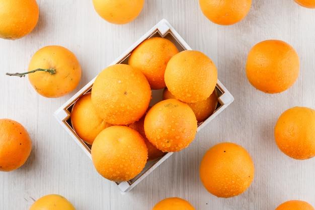 Pomarańcze w drewnianym pudełku na białej drewnianej powierzchni. leżał płasko.