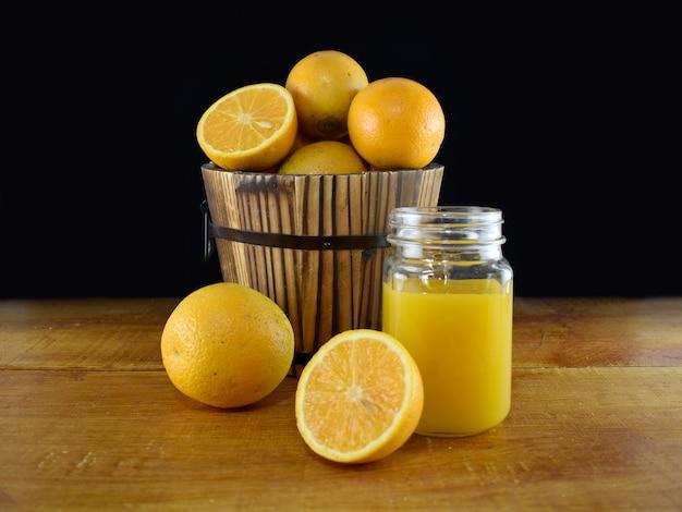 Pomarańcze w drewnianym wiadrze i szklance słoika z sokiem pomarańczowym