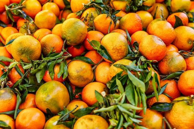 Pomarańcze z gałęziami i liśćmi na blacie. zbliżenie. . copyspace.