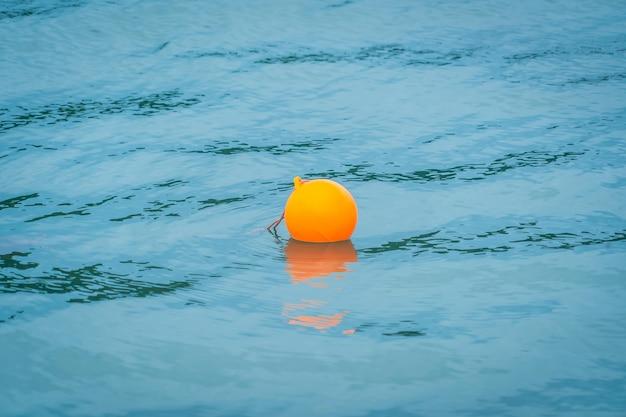 Pomarańczowa boja nawigacyjna pływająca na otwartym oceanie ostrzegająca o ruchu morskim