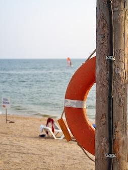 Pomarańczowa boja życia wisi na drewnianym filarze na piaszczystej plaży