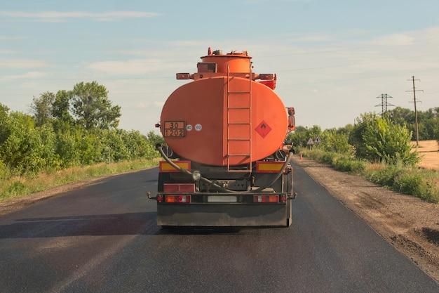 Pomarańczowa cysterna jedzie na wiejskiej drodze przeciw niebieskiemu niebu. widok z tyłu