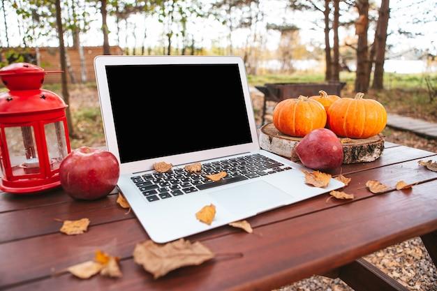 Pomarańczowa dynia i liście w pobliżu laptopa na stole. praca zdalna w kwarantannie. drewniany stół piknikowy w lesie jesienią. czas sezonu jesiennego