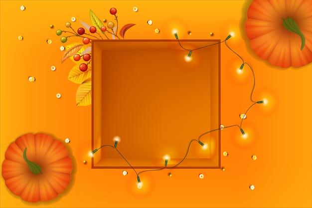 Pomarańczowa dynia i pudełko z girlandą na pomarańczowym tle tapeta szczęśliwego dziękczynienia jesień