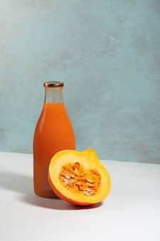 Pomarańczowa dynia i świeży sok z dyni w szklanej butelce na białym stole