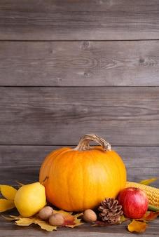 Pomarańczowa dynia z liśćmi i warzywami na szaro