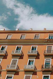 Pomarańczowa fasada hotelu w neapolu, włochy