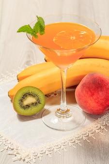 Pomarańczowa galaretka w szklance zwieńczonej listkami mięty, nektarynki, kiwi i banana na białej serwetce