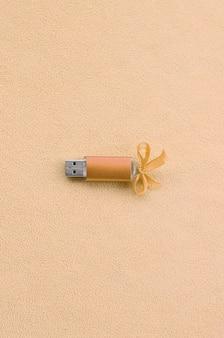 Pomarańczowa karta pamięci flash usb z niebieską kokardą leży na kocu z miękkiej, futrzanej, jasnopomarańczowej tkaniny polarowej.
