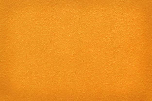 Pomarańczowa kolor betonowa ściana cementowa z detalem szorstkiego stiuku do prac tła i projektowania.