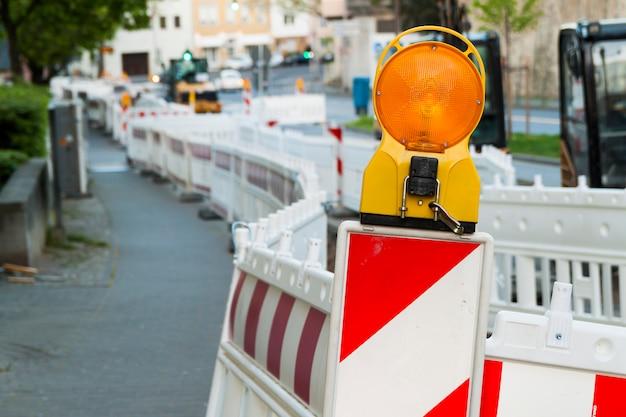 Pomarańczowa konstrukcja uliczne światło barierowe na barykadzie