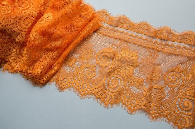 Pomarańczowa koronka leżąca na białej powierzchni