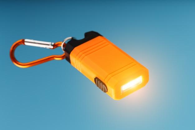 Pomarańczowa latarka led z karabińczykiem świeci na niebieskim tle.