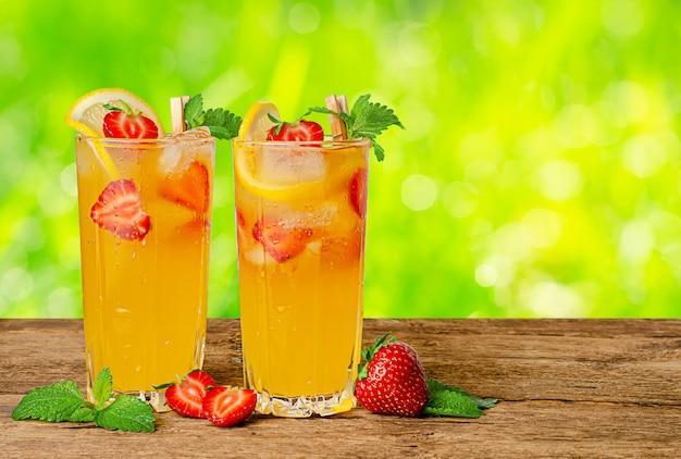 Pomarańczowa lemoniada z świeżymi truskawkami i mennicą na lata tle. skopiuj miejsce
