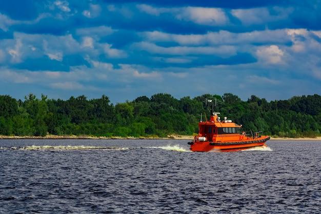 Pomarańczowa łódź pilotowa poruszająca się nad rzeką w europie. służba ratunkowa