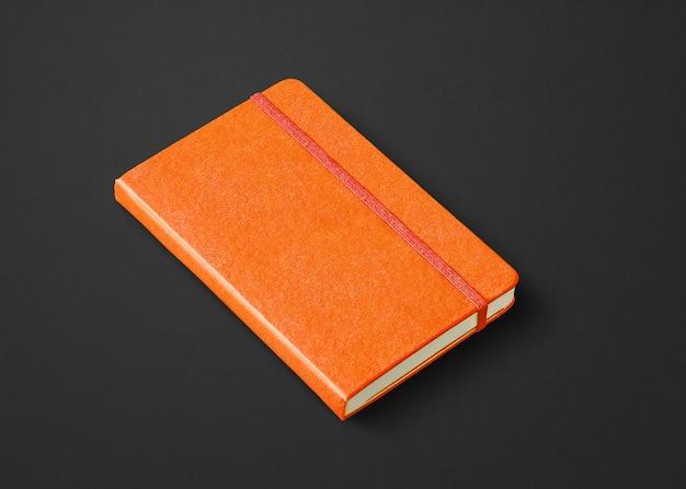 Pomarańczowa makieta zamkniętego notebooka na czarnym tle