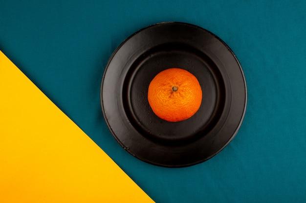 Pomarańczowa mandarynka widok z góry świeżego, dojrzałego, łagodnego soczystego całego czarnego talerza na żółto-niebieskiej podłodze