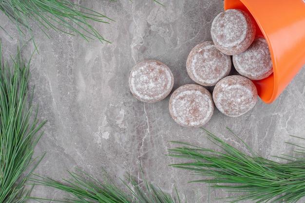 Pomarańczowa miska pełna słodkich ciasteczek na marmurowej powierzchni.