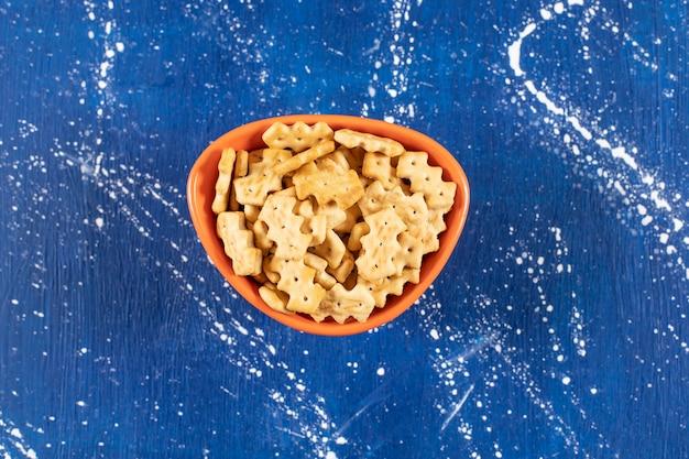 Pomarańczowa miska słonych małych krakersów na marmurowej powierzchni